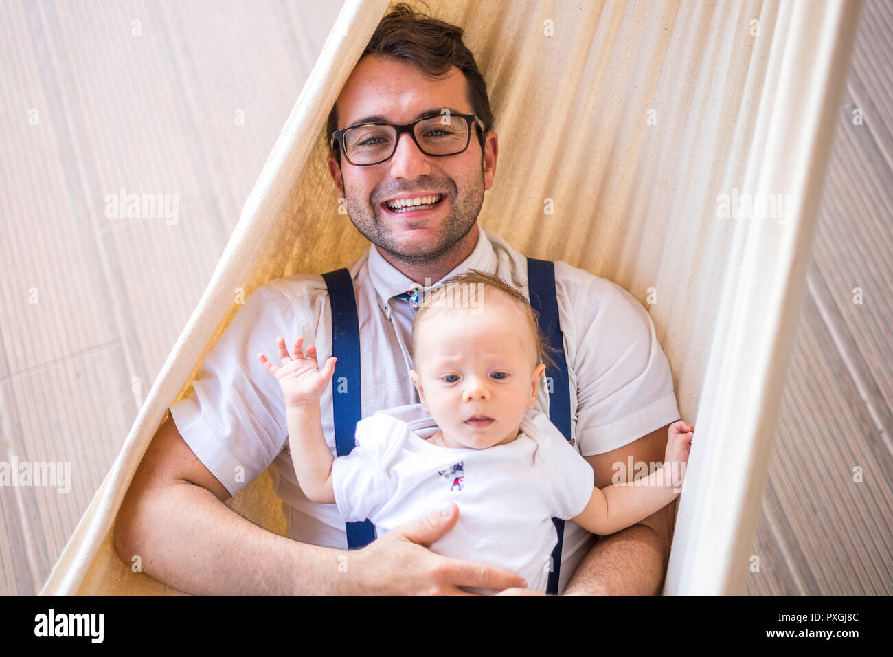 Young man with four months baby boy relaxing on hammock - Stock Image