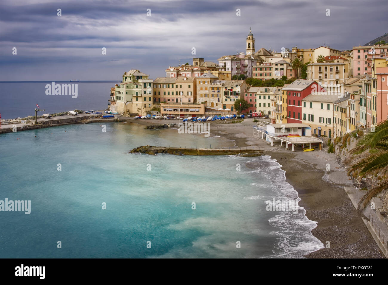 Waterfront and beach at Bogliasco, Italy with gentle surf lapping the sandy shore in front of colorful buildings under a cloudy sky in a tourism and t - Stock Image