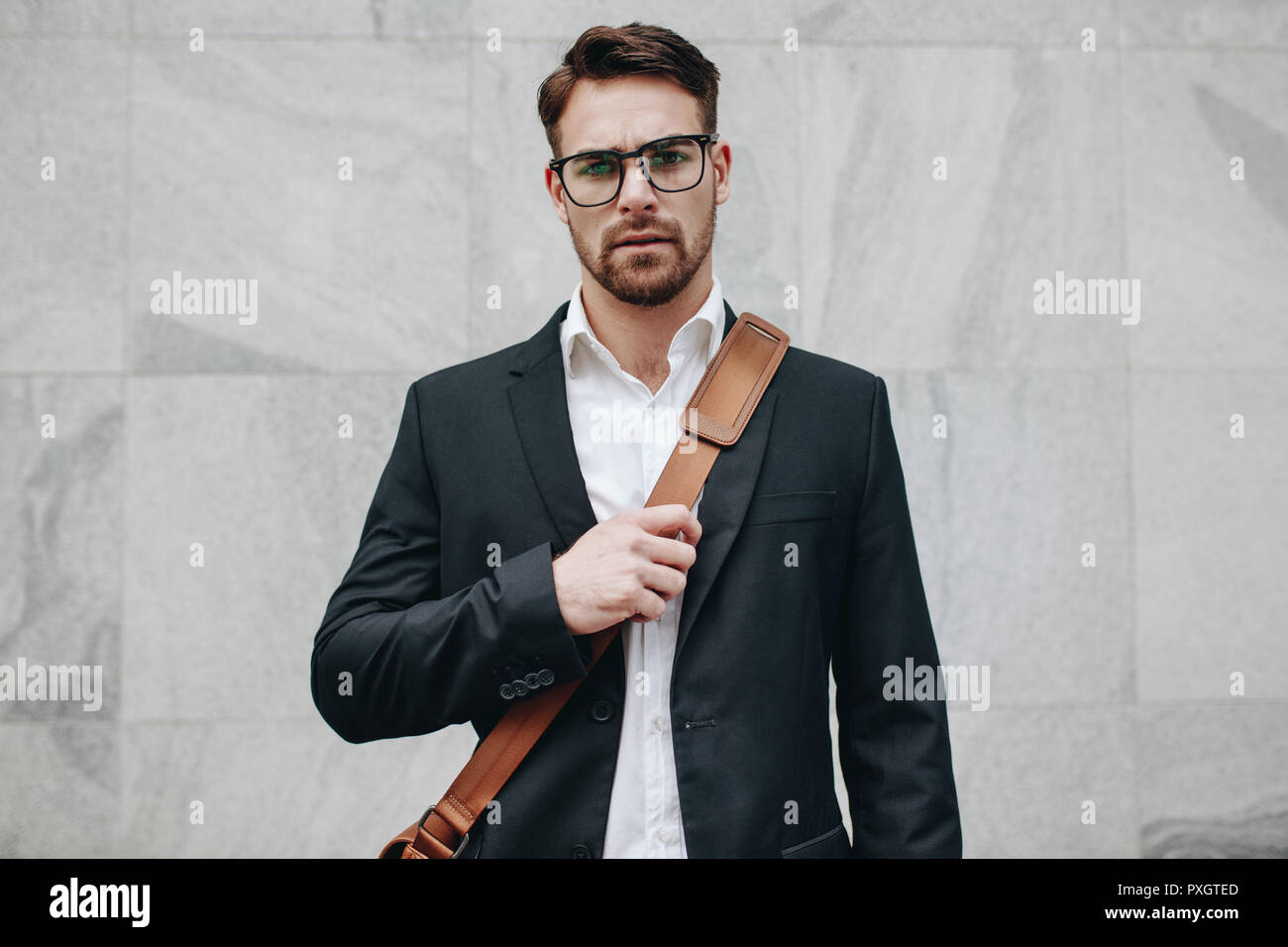 Businessman standing against a tiled wall wearing an office bag. Young man wearing eyeglasses and carrying an office bag standing outdoors. - Stock Image