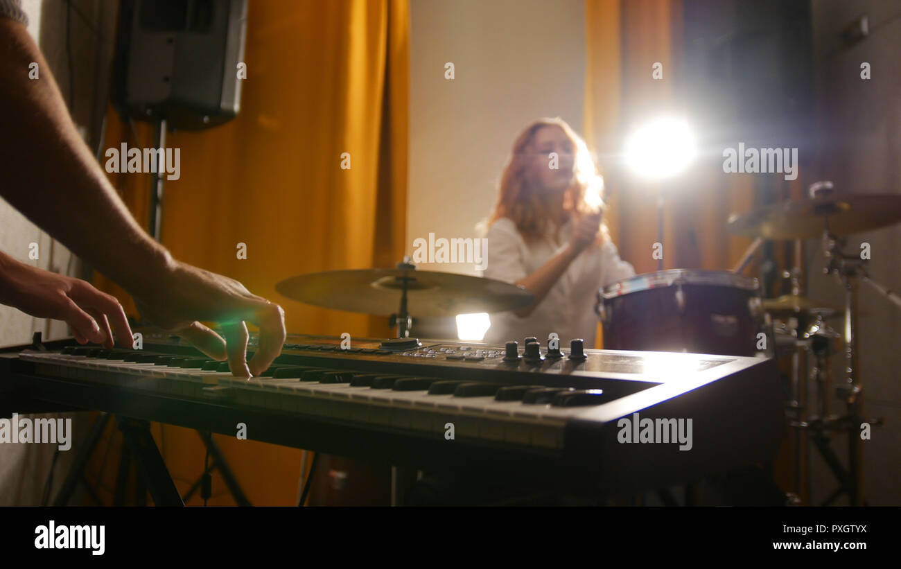 Repetition. Girl drummer and a guy on keyboards. - Stock Image