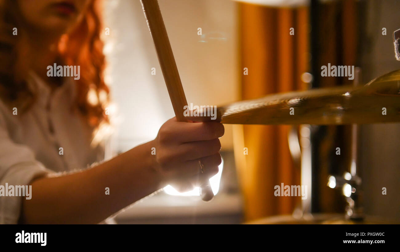 Repetition. Redhead girl drummer holds the hi-hat. Close up - Stock Image