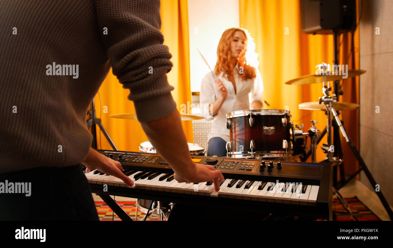 Girl drummer and a guy on keyboards. Focus from hands to drums. - Stock Image