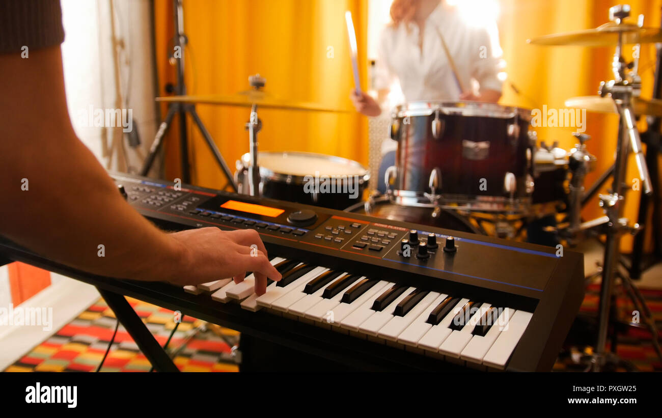 Repetition. Girl drummer and a guy on keyboards. Focus on keyboard - Stock Image