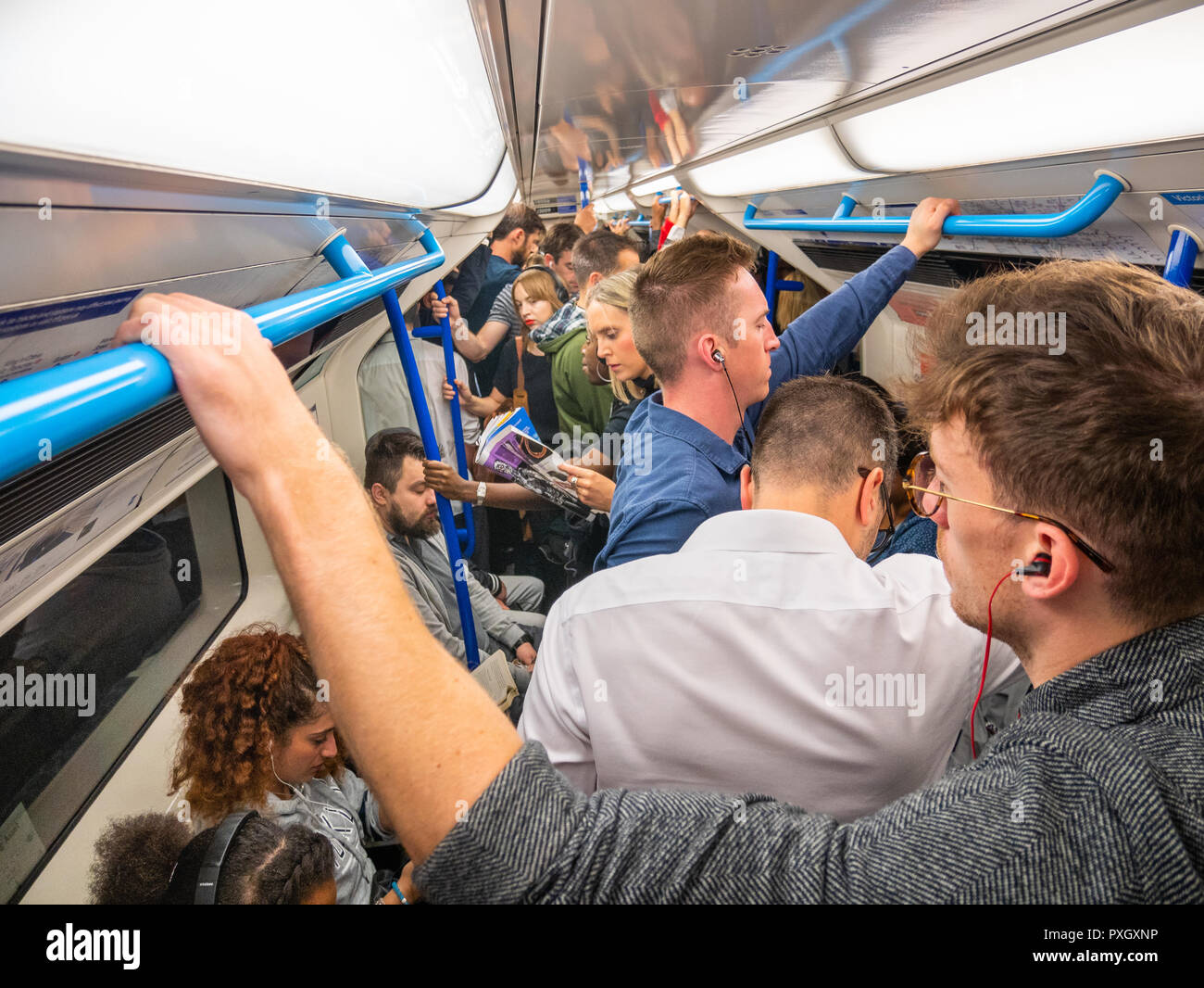Commuters on crowded London Underground during rush hour, UK - Stock Image