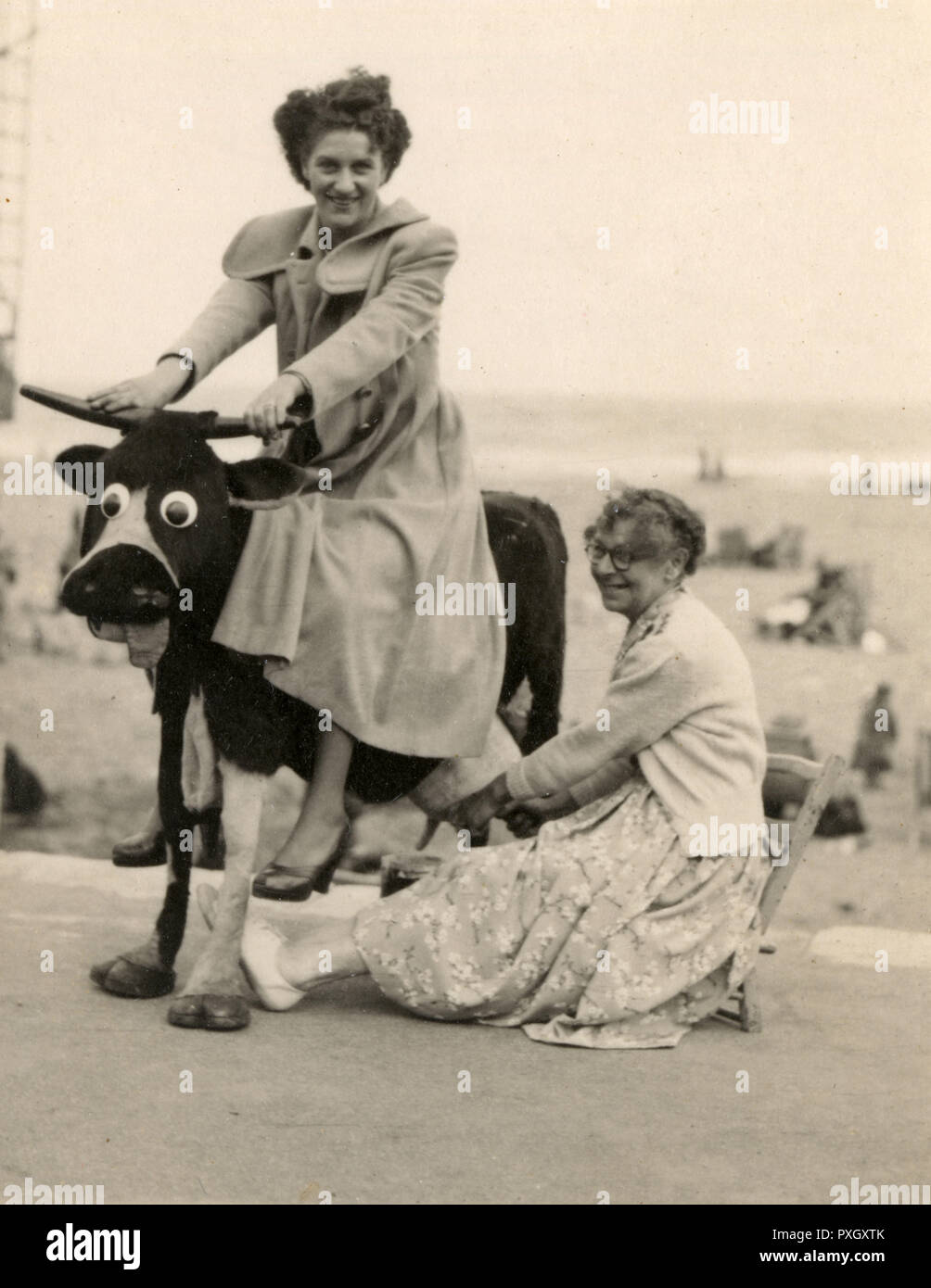 Two ladies posing for a comedy photograph at an unidentified British seaside resort.  One sits on a fake cow while the other pretends to milk it from some alarmingly authentic looking udders!     Date: 1950s - Stock Image