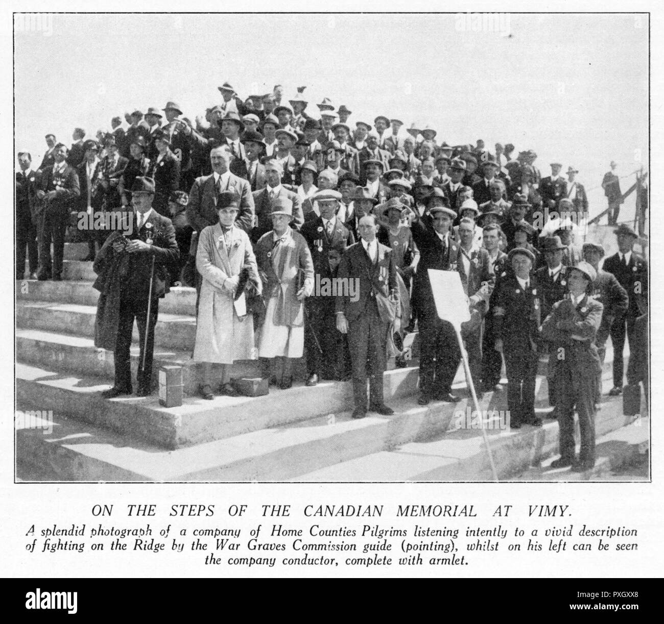 A group of Home Counties pilgrims on the steps of the Canadian Memorial at Vimy, listening to a War Graves Commission guide describing the fighting. The pilgrimage of 11,000 people to France and Flanders was organised by the British Legion and attended by the Prince of Wales.       Date: 1928 - Stock Image
