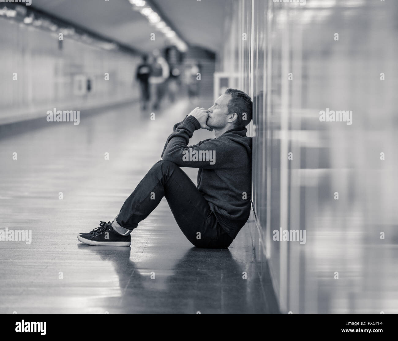 Miserable jobless young man crying Drug addict Homeless in depression stress sitting on ground street subway tunnel looking desperate leaning on wall  - Stock Image