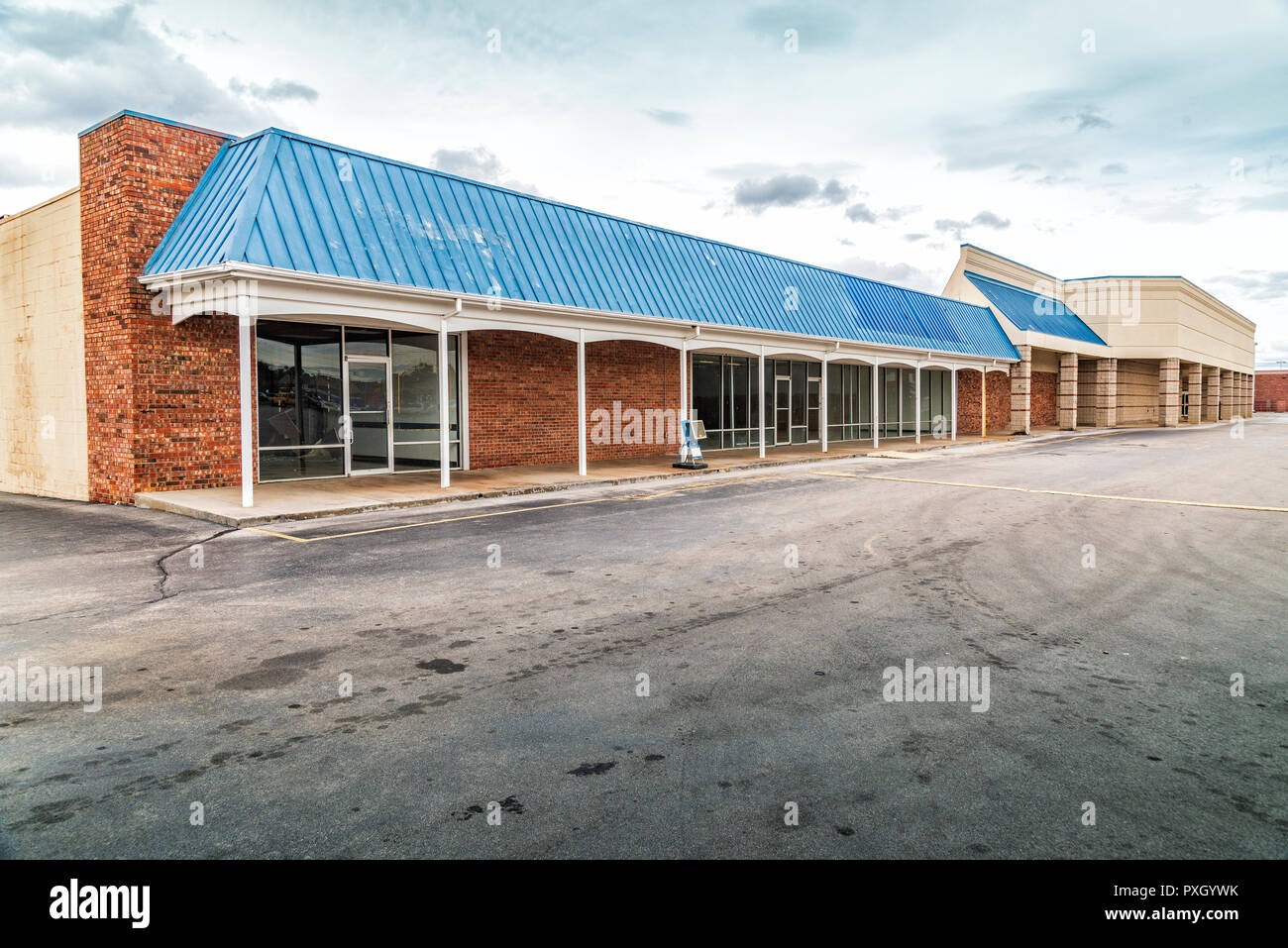 Horizontal shot of an old vacant stip shopping center with an empty parking lot and cloudy sky. - Stock Image
