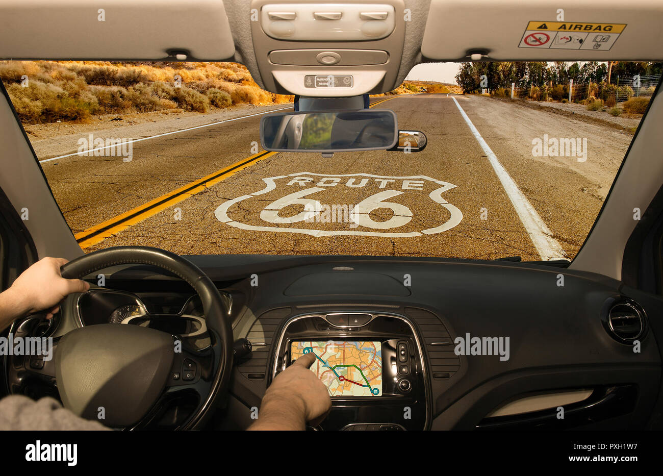 Driving a car while using the touch screen of a GPS navigation system on the Historic Route 66 in California, USA - Stock Image