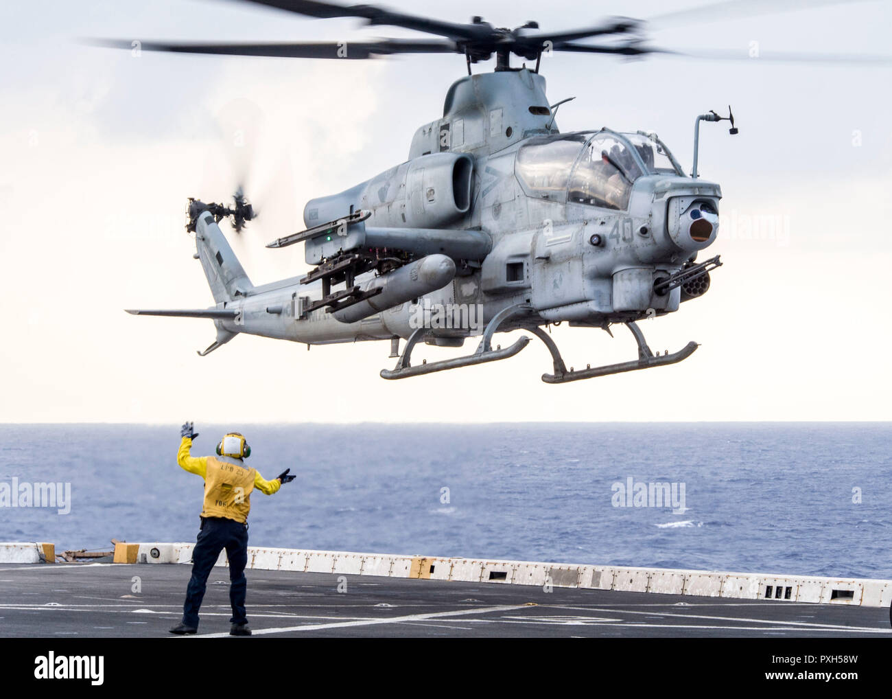 181020-N-PH222-1299 MEDITERRANEAN SEA (Oct. 20, 2018) Aviation Boatswain's Mate (Handling) Airman Eddie De La Cruz, signals an AH–1Z Viper helicopter, attached to Marine Medium Tiltrotor Squadron (VMM) 166 (Reinforced), from the flight deck of the San Antonio-class amphibious transport dock ship USS Anchorage (LPD 23) during flight operations in the Mediterranean Sea, Oct. 20, 2018. Anchorage and embarked 13th Marine Expeditionary Unit are deployed to the U.S. 6th Fleet area of operations as a crisis response force in support of regional partners as well as to promote U.S. national security in - Stock Image