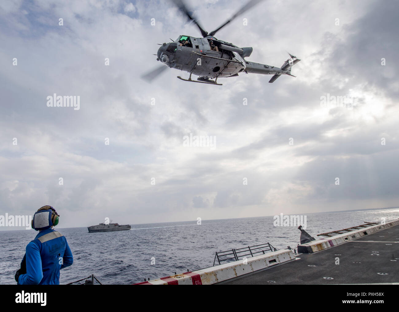 181020-N-PH222-1563 MEDITERRANEAN SEA (Oct. 20, 2018) Damage Controlman 3rd Class Wayne L. Batten, watches a UH-1Y Venom helicopter, attached to Marine Medium Tiltrotor Squadron (VMM) 166 (Reinforced), take off from the flight deck of the San Antonio-class amphibious transport dock ship USS Anchorage (LPD 23) during flight operations with the Spearhead-class expeditionary fast transport ship USNS Carson City (T-EPF-7) in the Mediterranean Sea, Oct. 20, 2018. Anchorage and embarked 13th Marine Expeditionary Unit are deployed to the U.S. 6th Fleet area of operations as a crisis response force in - Stock Image