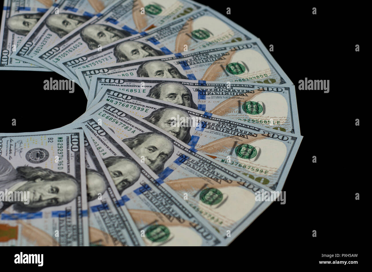 One hundred dollar bills are fanned out on a black background. - Stock Image