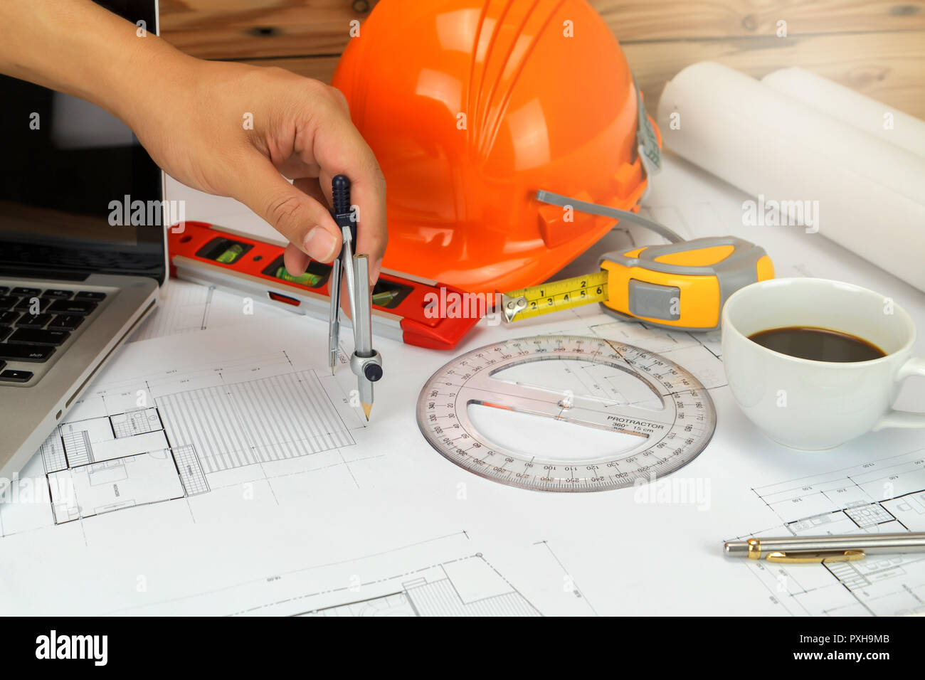 An architect or engineer working on blueprint, An architect or engineer uses a divider gauge on the blueprint., architectural concept - Stock Image
