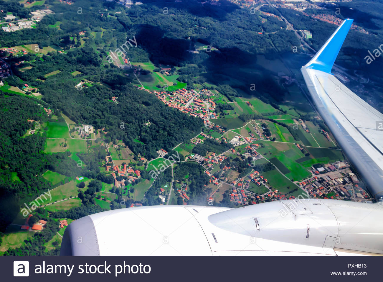 View from airplane window above human settlement. Plane wjite turbine and wing. - Stock Image