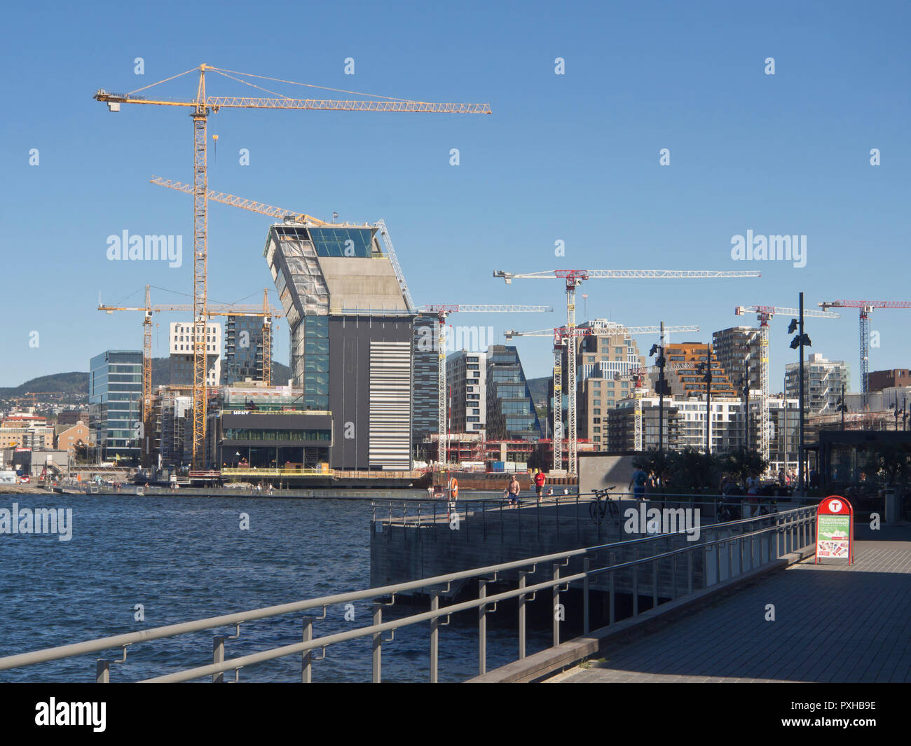 Busy building activity in the Bjørvika district of Oslo Norway.The angled construction of the new Munch museum rising by the Oslo Fjord - Stock Image