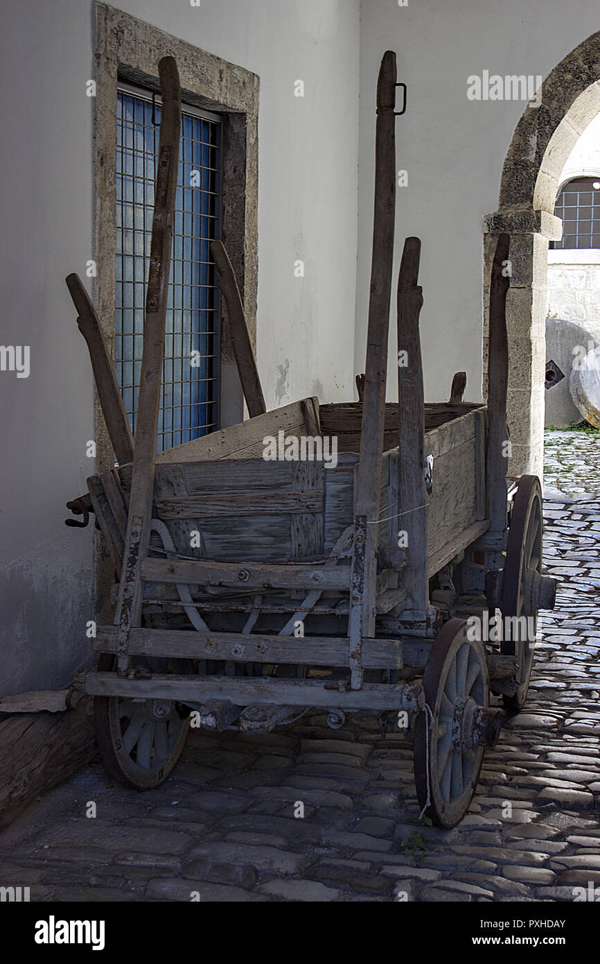 An old carriage that binds to a horse. The plow and blade are loaded on the carriage. - Stock Image