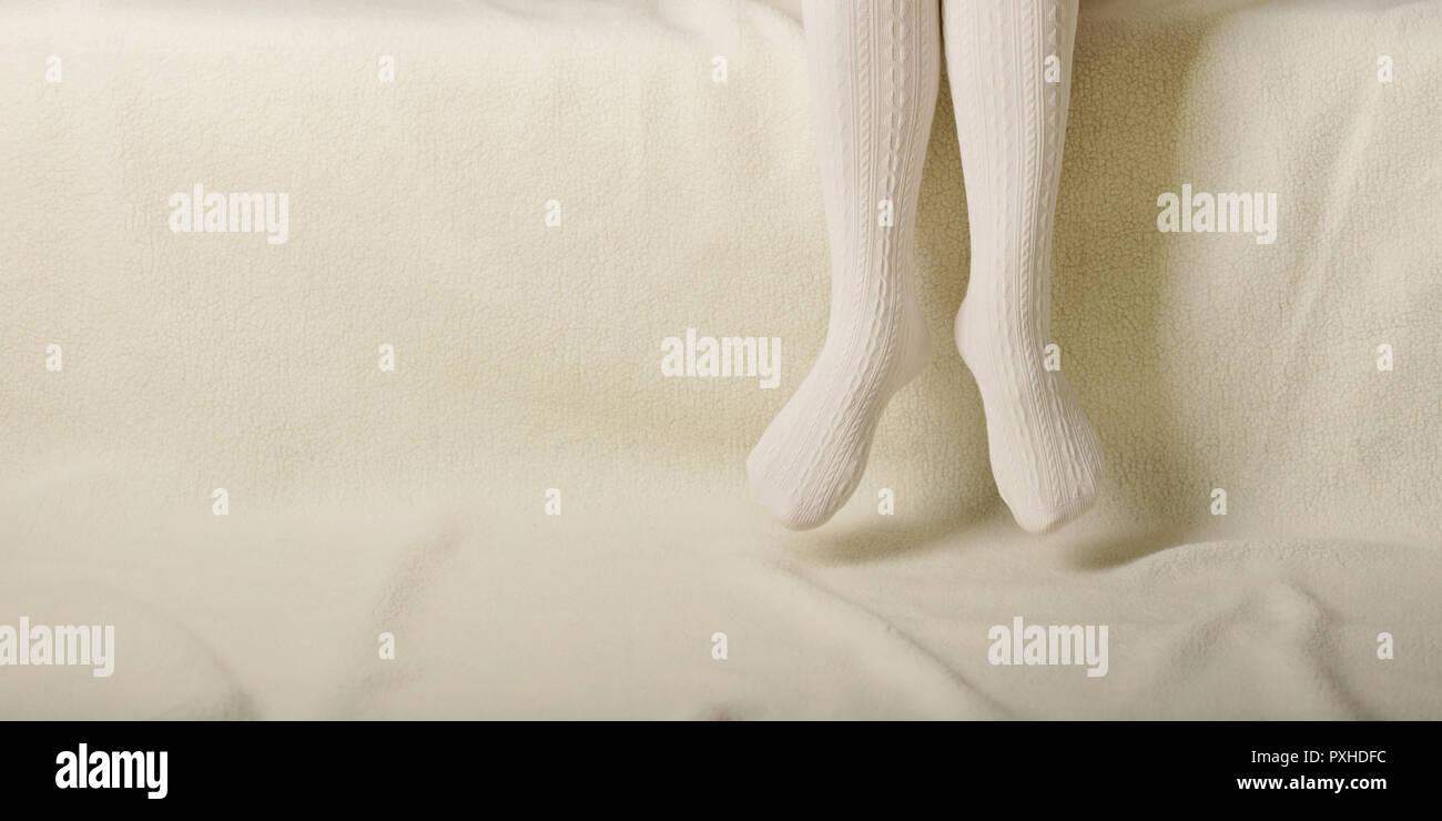 Female legs in warm white knitted tights on a white background made of faux fur - Stock Image