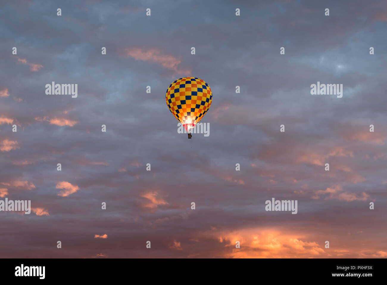 Colorful hot air balloon in yellow, orange, and dark blue colors glowing against a dramatic colorful sky and clouds at sunrise Stock Photo