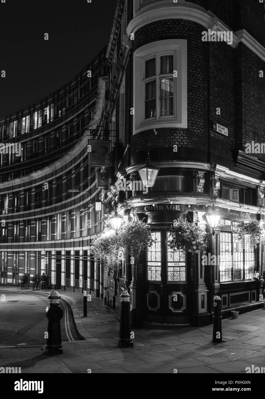 Night image of The Cockpit public house with hanging flower baskets on St Andrews Hill, London - Stock Image
