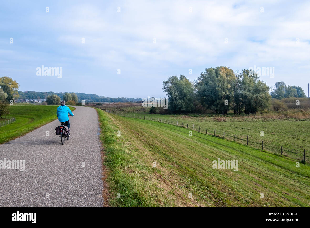 Woman on a bicycle on the dike along the flood plains along the river Nederrijn in Wageningen, the Netherlands. Stock Photo