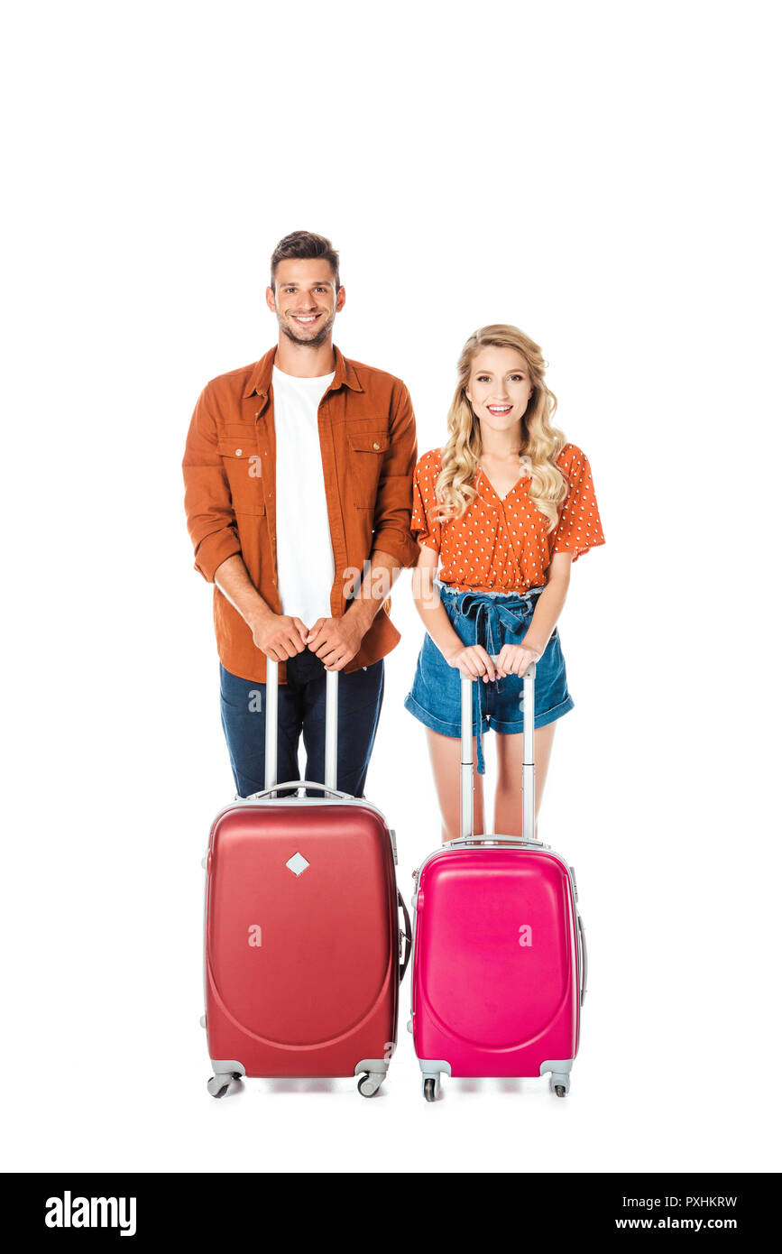 happy young couple with suitcases looking at camera isolated on white - Stock Image