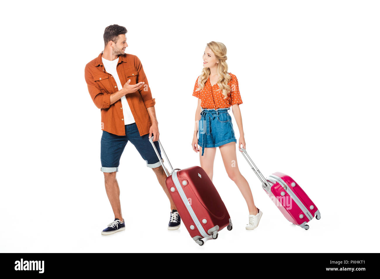 happy young couple with luggage walking and chatting isolated on white - Stock Image