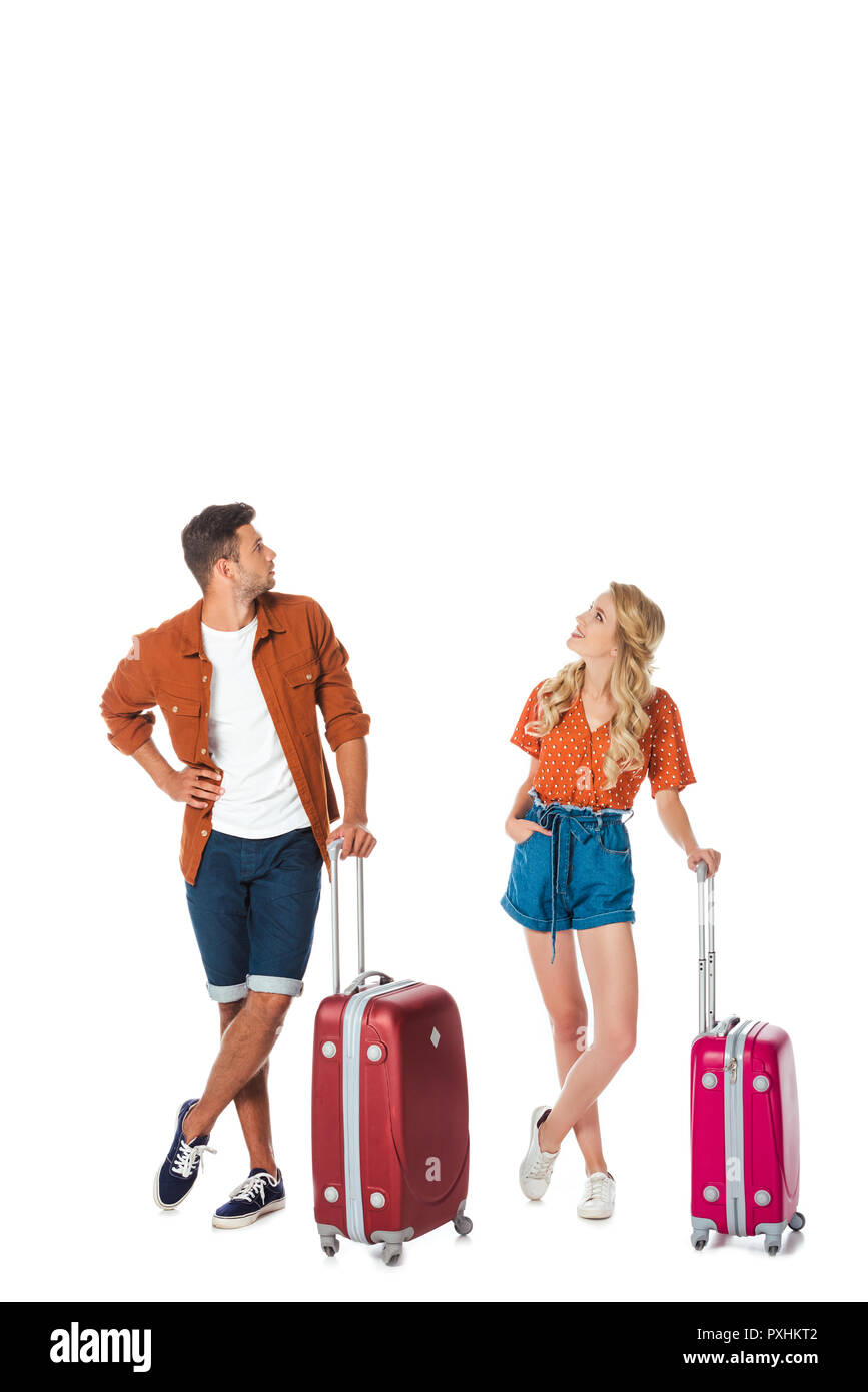 young couple with luggage looking up isolated on white - Stock Image
