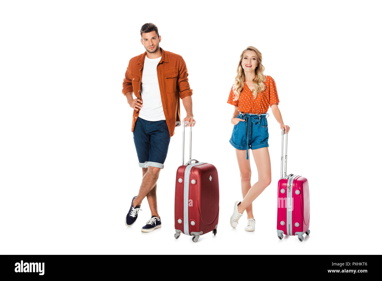 attractive young couple with suitcases looking at camera isolated on white - Stock Image