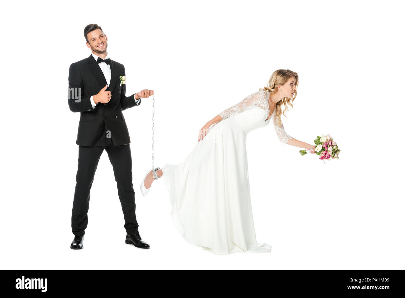 happy groom holding chain tied around brides leg and showing thumb up isolated on white - Stock Image