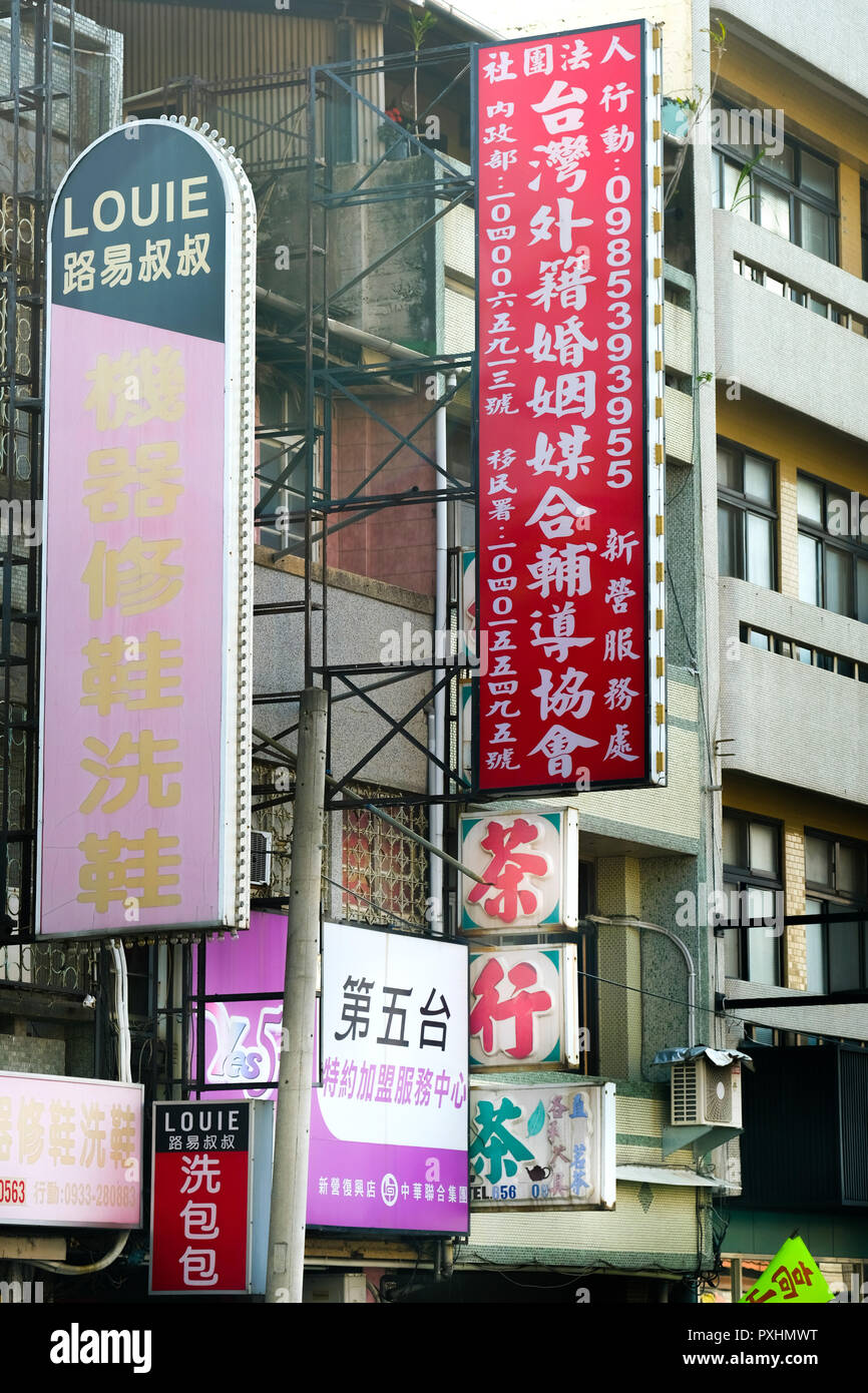 Wedding Agency (billboard top right) advertises Vietnamese brides abroad, location Xinying, Taiwan - Stock Image