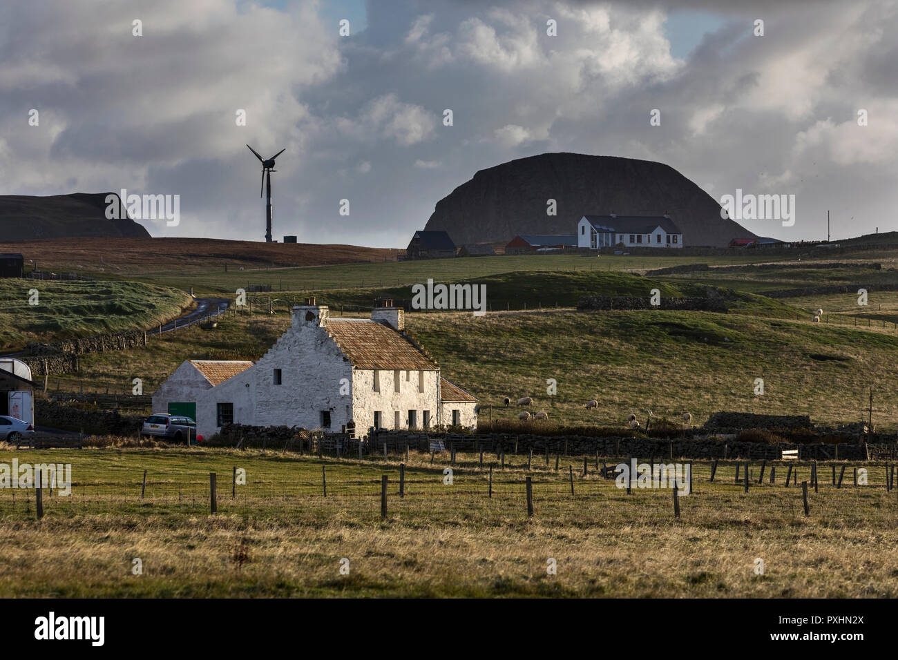Fair Isle showing one of the new wind turbines and croft houses - Stock Image