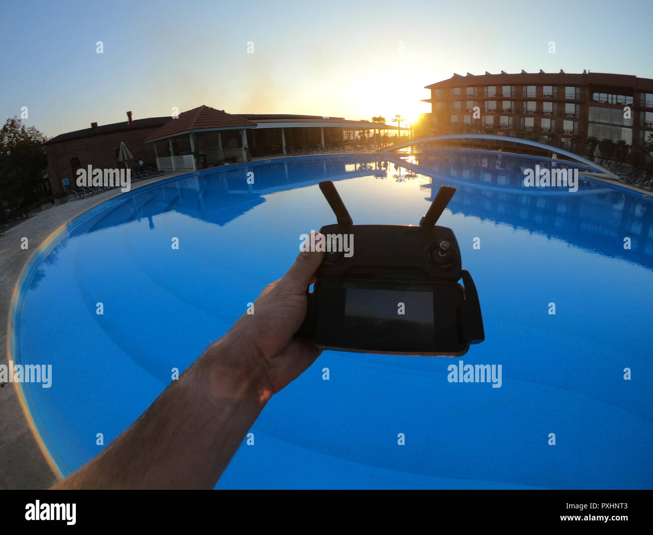 Drone remote by the pool at sunset in the hotel - Stock Image