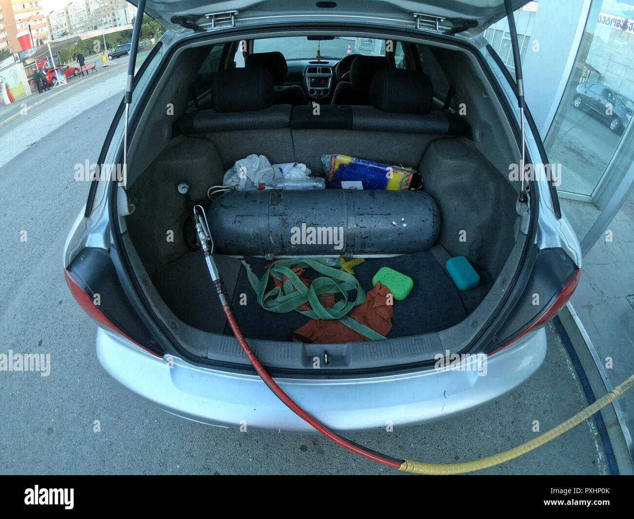 Filling the car with methane gas bottle in the trunk Stock Photo