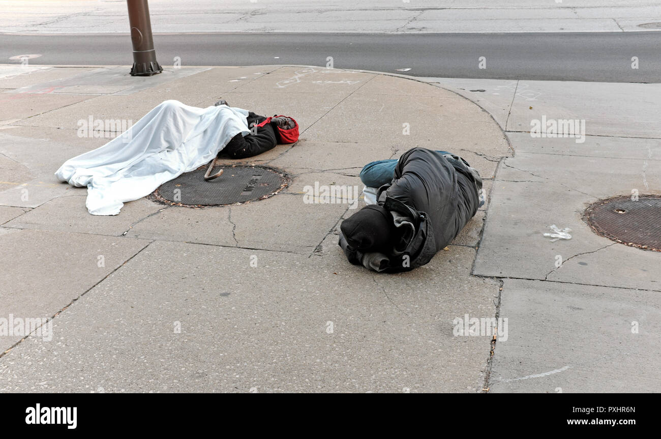 Two homeless men sleep on a downtown Cleveland, Ohio street during the late fall chill. - Stock Image