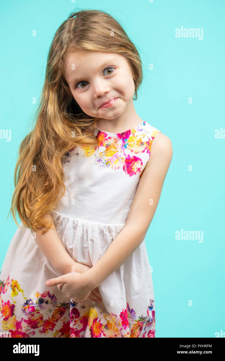 4de2ac44fc08f Cute small girl wearing a flowers summer dress isolated on blue ...