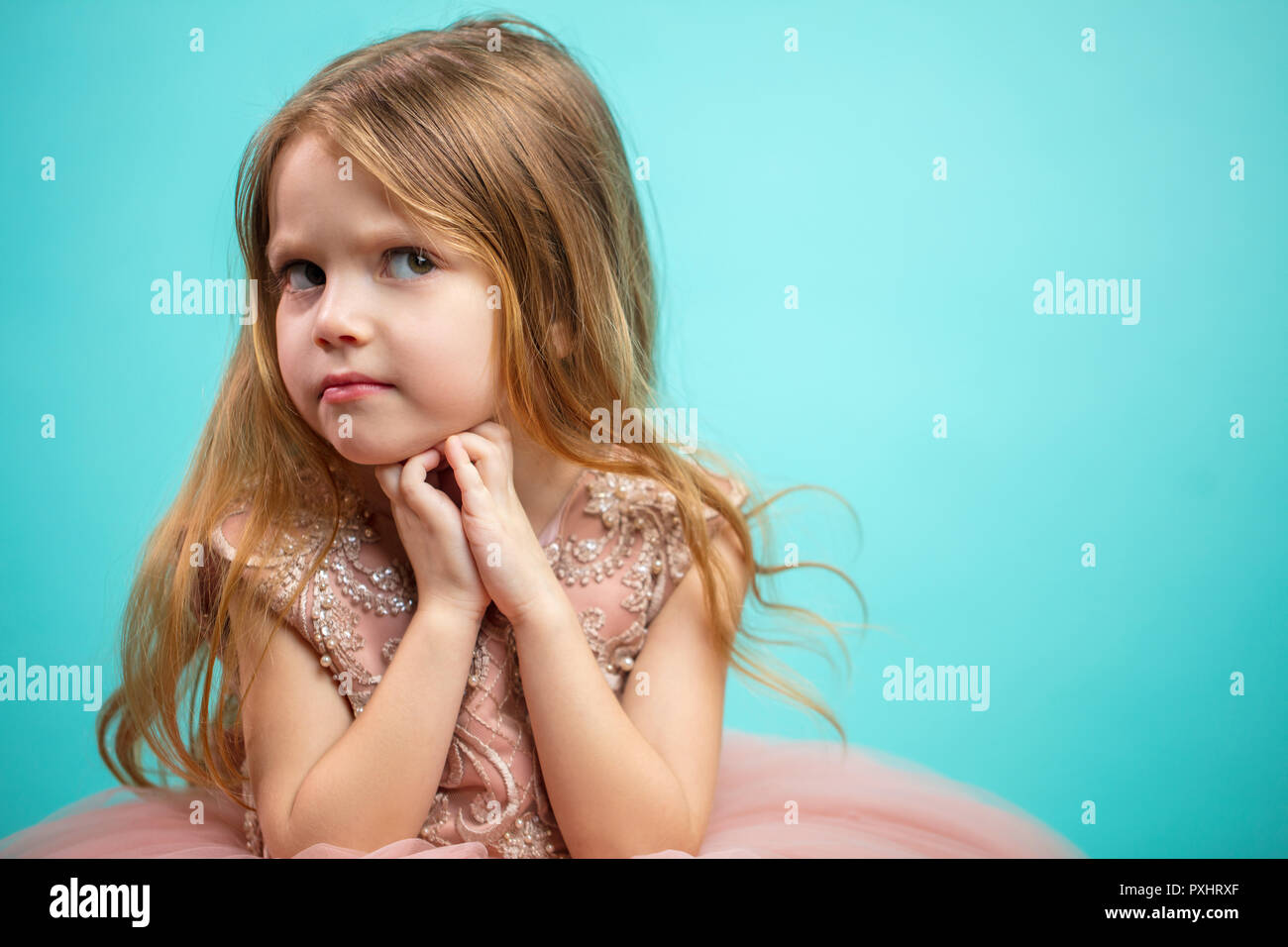 Little Caucasian female child in pink dress with naughty and resentful face expression. - Stock Image