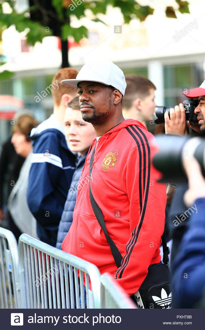 A Black Male Youth In Manchester United Tracksuit Top Looks On During English Defence League Demonstration At Manchester Stand Up To Racism Protest - Stock Image