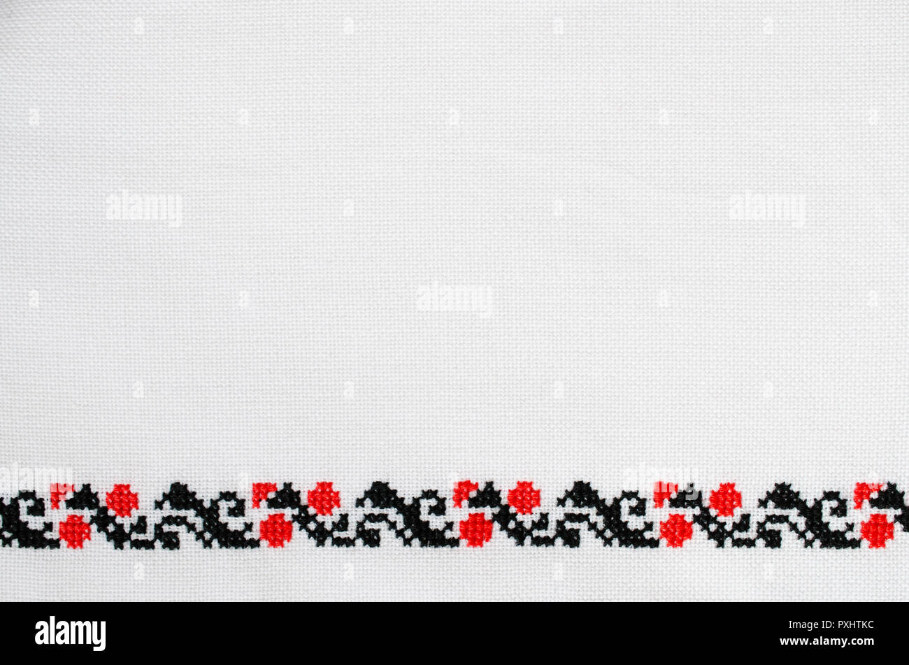 Texture of White Canvas With Slavic Red and Black Embroidery by Cross-stitch. Ukrainian Embroidery for Background. - Stock Image