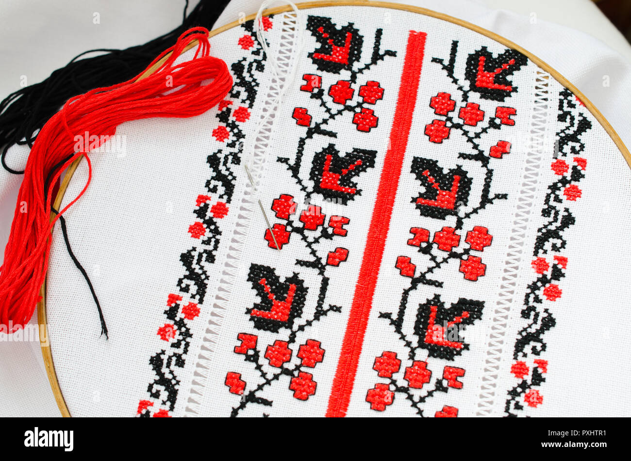 The wooden hoop with the embroidery pattern of red and Black color on canvas. Slavic Embroidery with hemming. - Stock Image