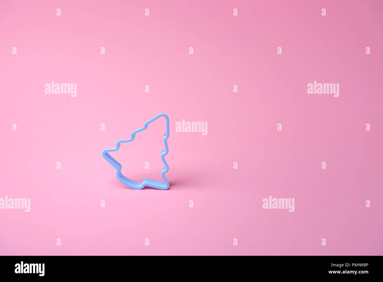 Single blue cookies cutter in shape of a Christmas tree, on a pink background. Xmas baking concept. Minimalist culinary image. - Stock Image