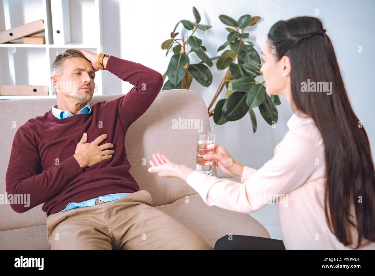 psychotherapist giving glass of water and pill to patient with heartache - Stock Image