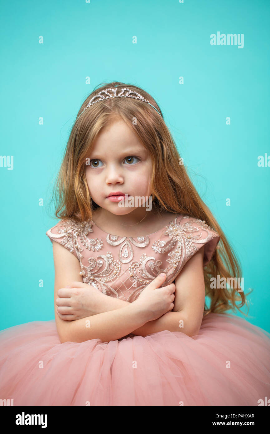 Little Caucasian female child in pink dress with naughty and res - Stock Image
