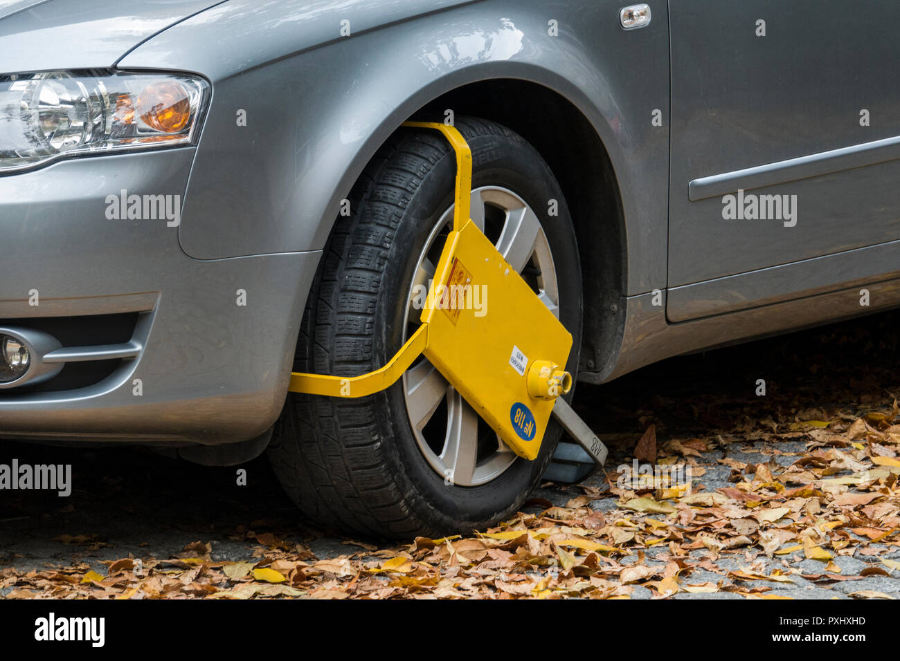 Yellow wheel clamp on parked car in Plovdiv, Bulgaria - Stock Image