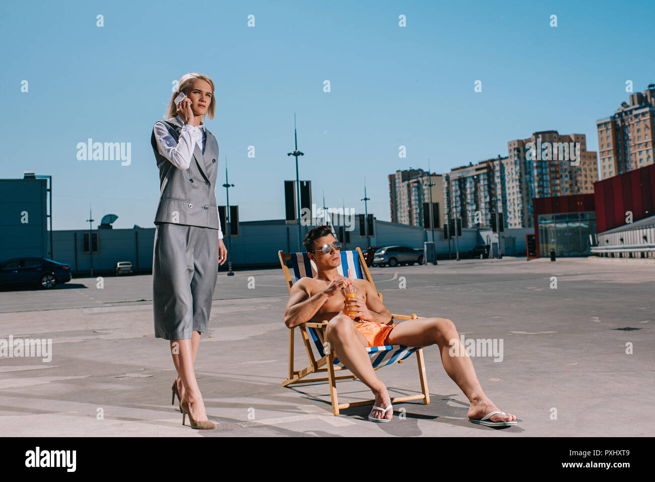 attractive young man relaxing on sun lounger while his lady boss in suit next to him and talking by phone on parking Stock Photo