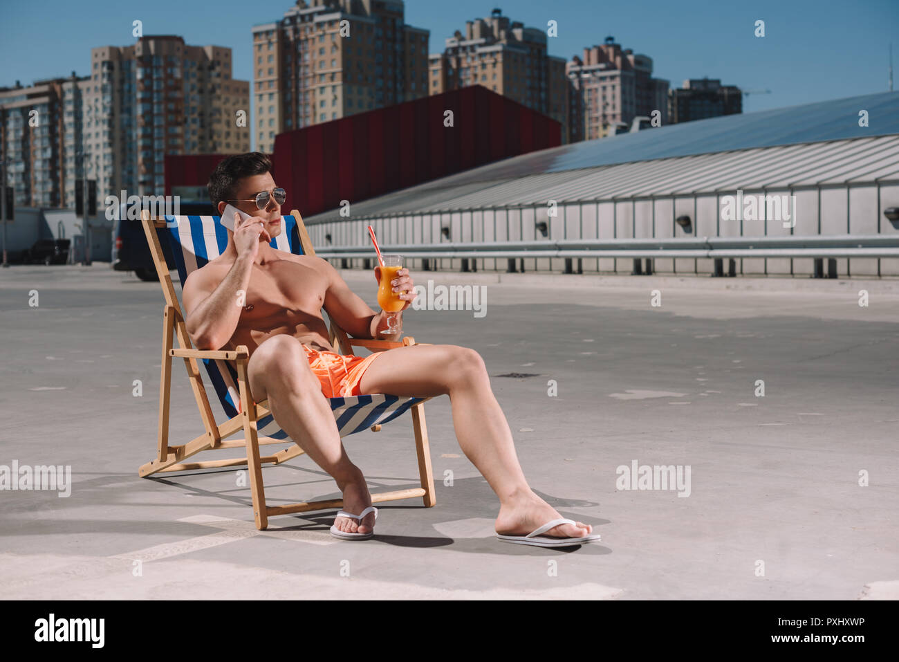 handsome young shirtless man relaxing on sun lounger with cocktail and talking by phone on parking Stock Photo