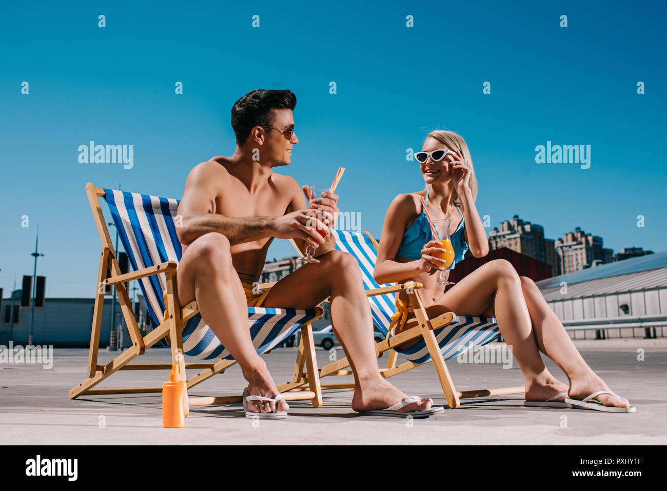 young couple with refreshing cocktails sitting on sun loungers on parking - Stock Image