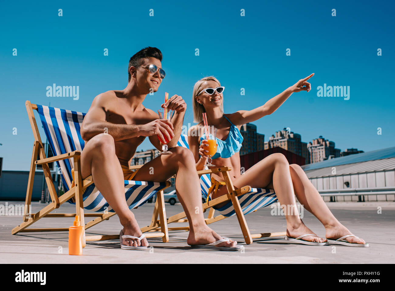 young couple with cocktails sitting on sun loungers on parking - Stock Image