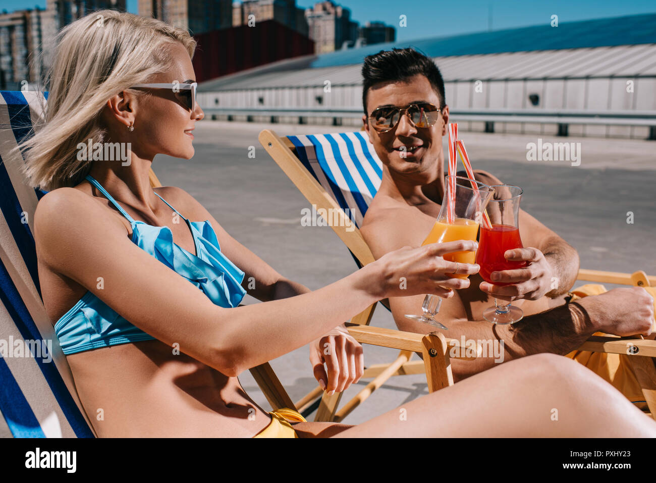 young couple clinking glasses of cocktails while sitting on sun loungers on parking - Stock Image