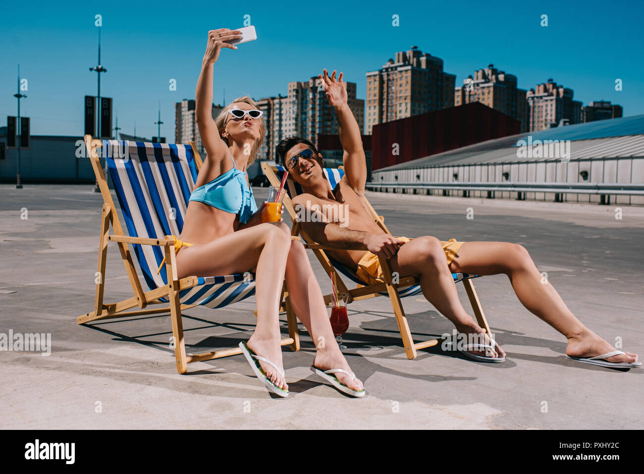 young couple relaxing on sun loungers with cocktails and taking selfie on parking - Stock Image