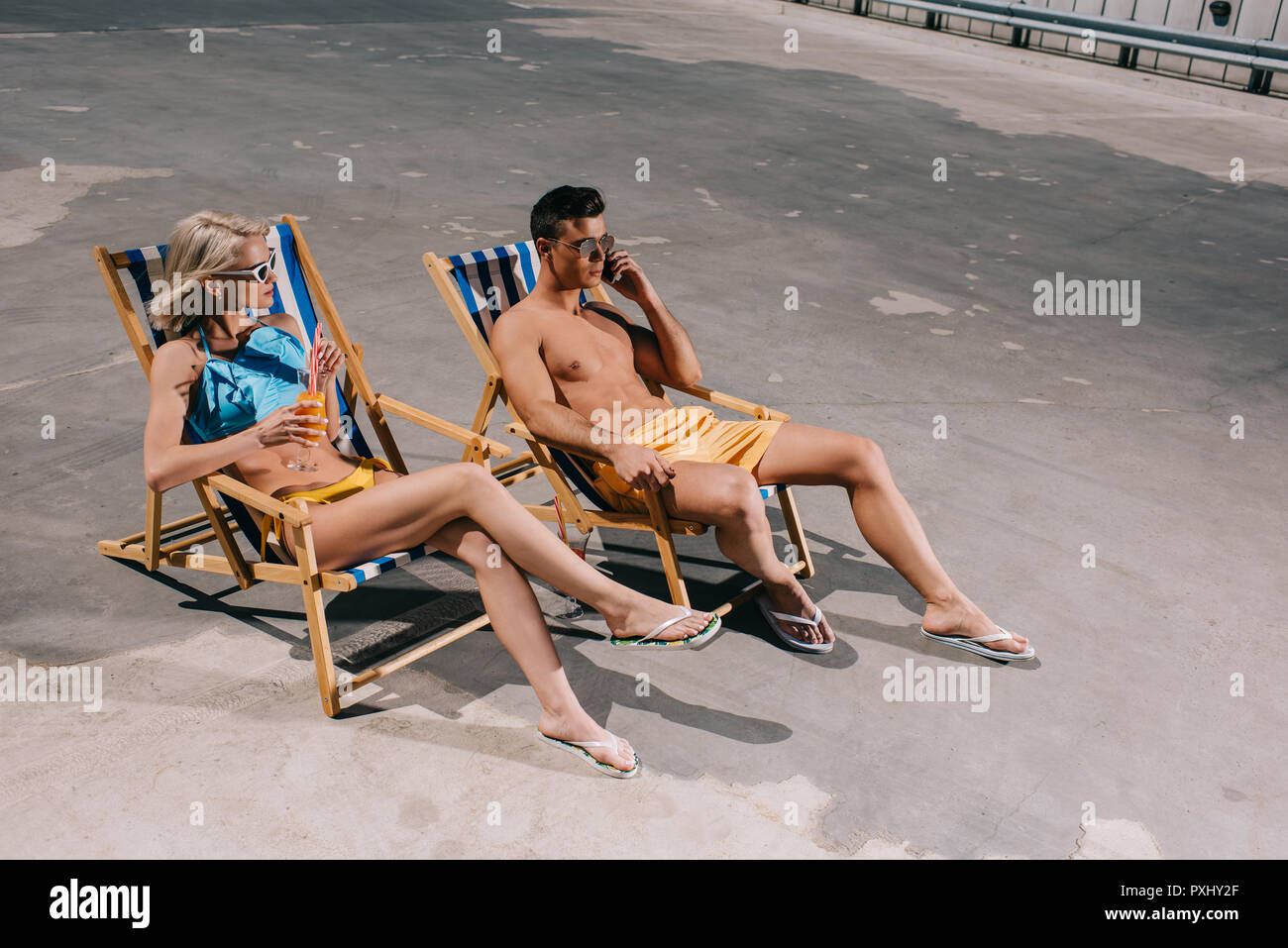 high angle view of young couple relaxing on sun loungers relaxing on parking - Stock Image